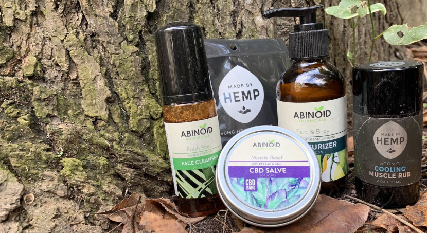 Abinoid and Made By Hemp CBD Products on a tree stump